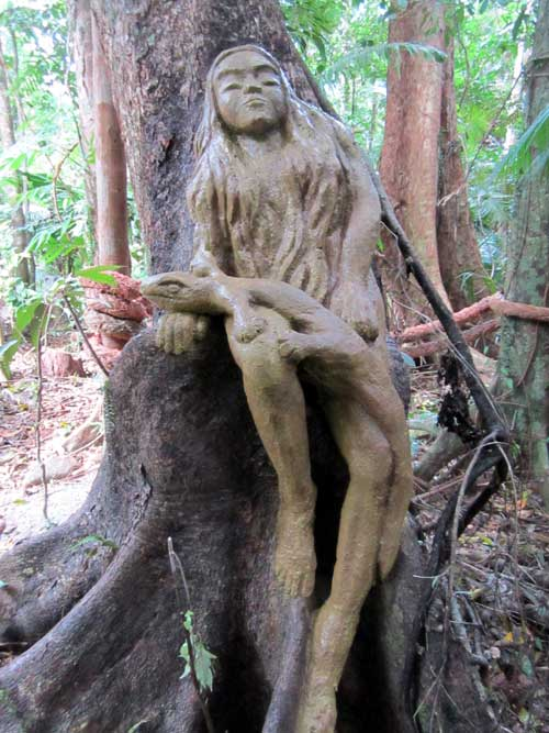 cement sculpture of girl in tree